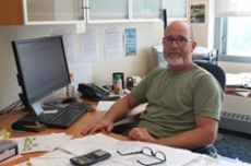 James Hewett sitting at his desk